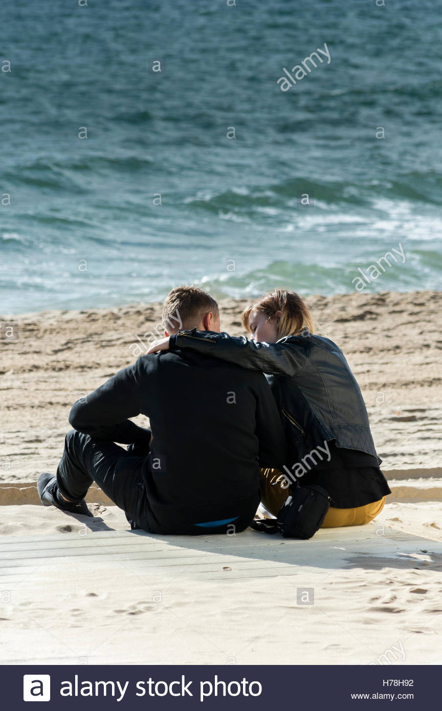 Young couple sitting close on the sandy beach, Bournemouth, Dorset, England - Stock Image