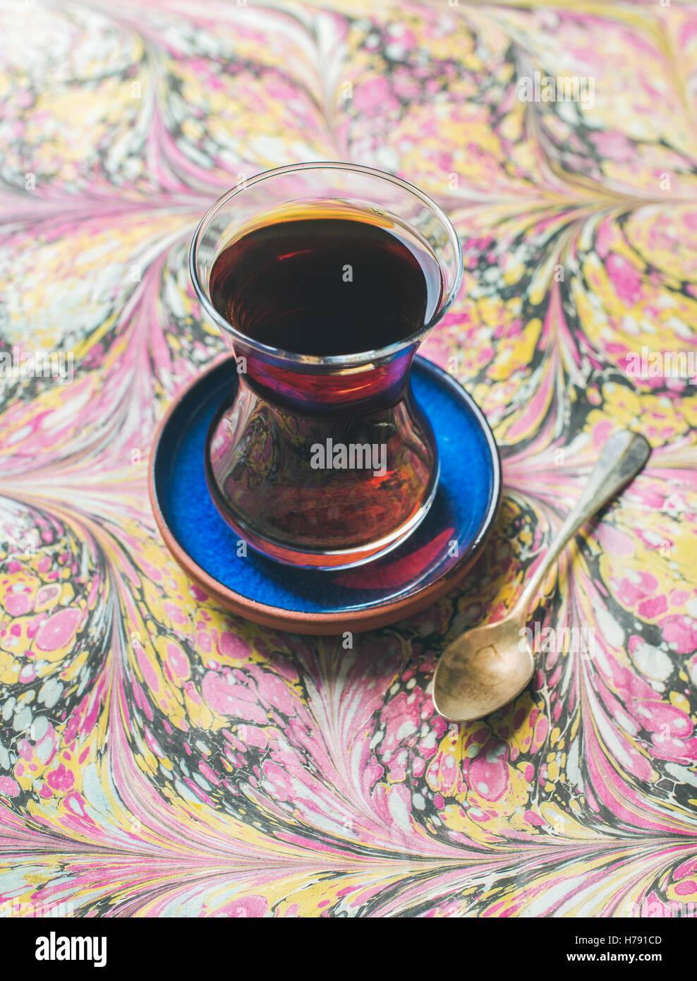 Turkish tea in traditional oriental tulip glass over colorful background - Stock Image