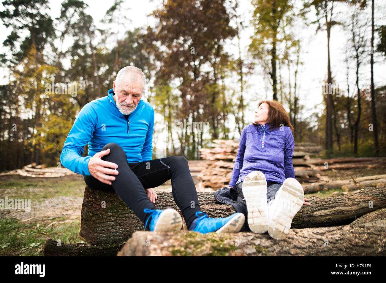 Senior runners sitting on wooden logs, resting. Autumn nature. - Stock Image