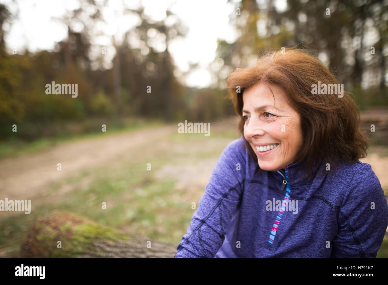 Senior runner sitting on wooden logs, woman resting, smiling. - Stock Image