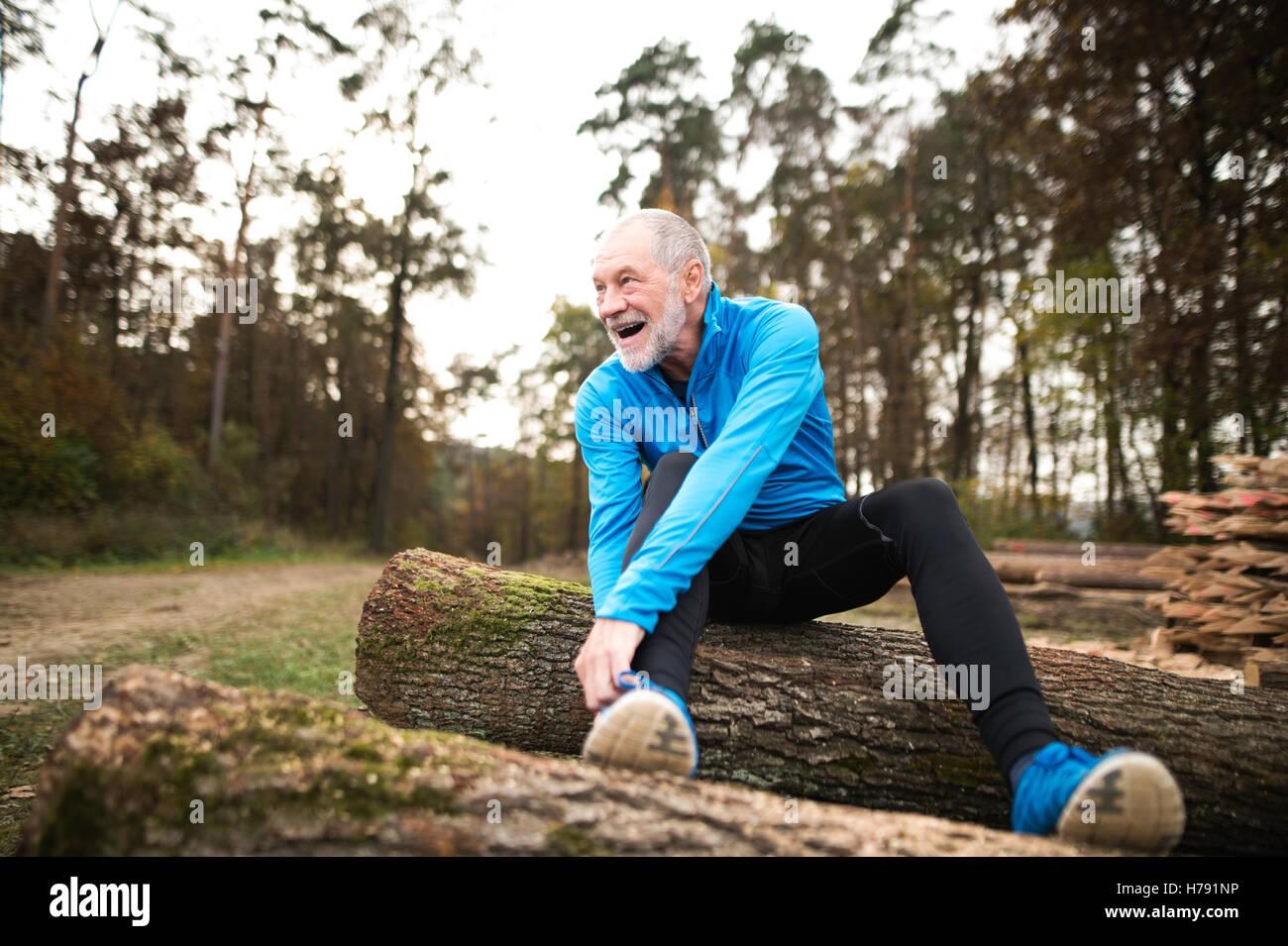 Senior runner sitting on wooden logs, man resting, stretching. - Stock Image
