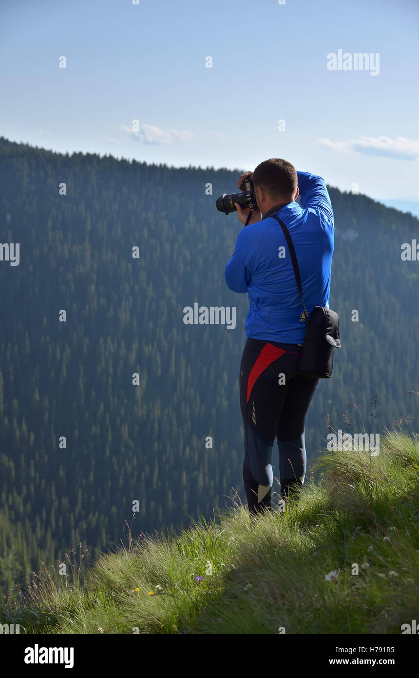 Photographer on a mountain peak shooting the landscape - Stock Image