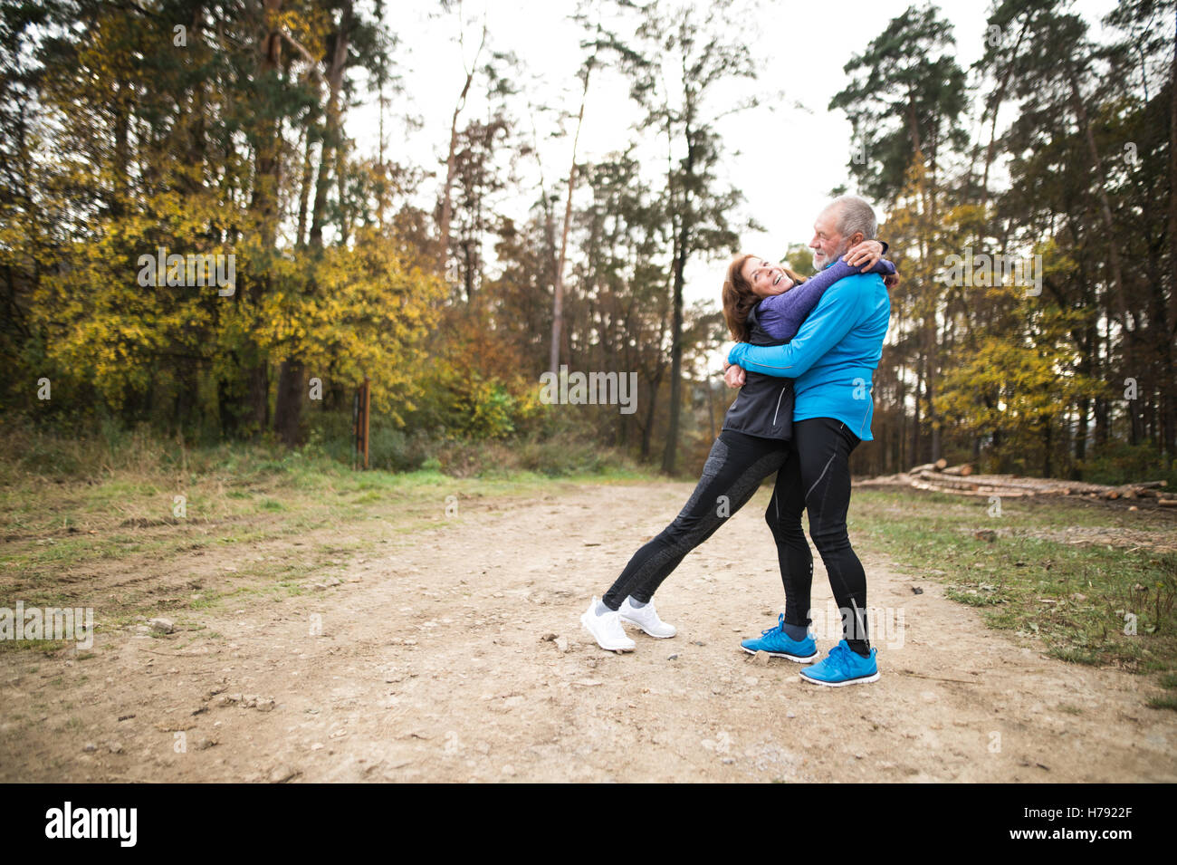 Beautiful senior couple running outside in sunny autumn forest - Stock Image