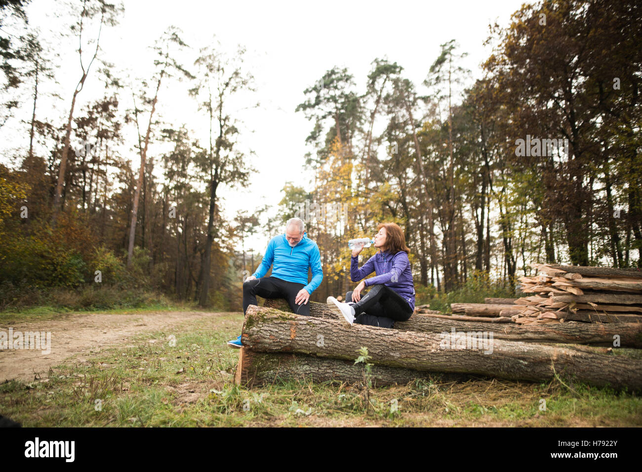 Senior runners sitting on wooden logs, resting, drinking water. - Stock Image