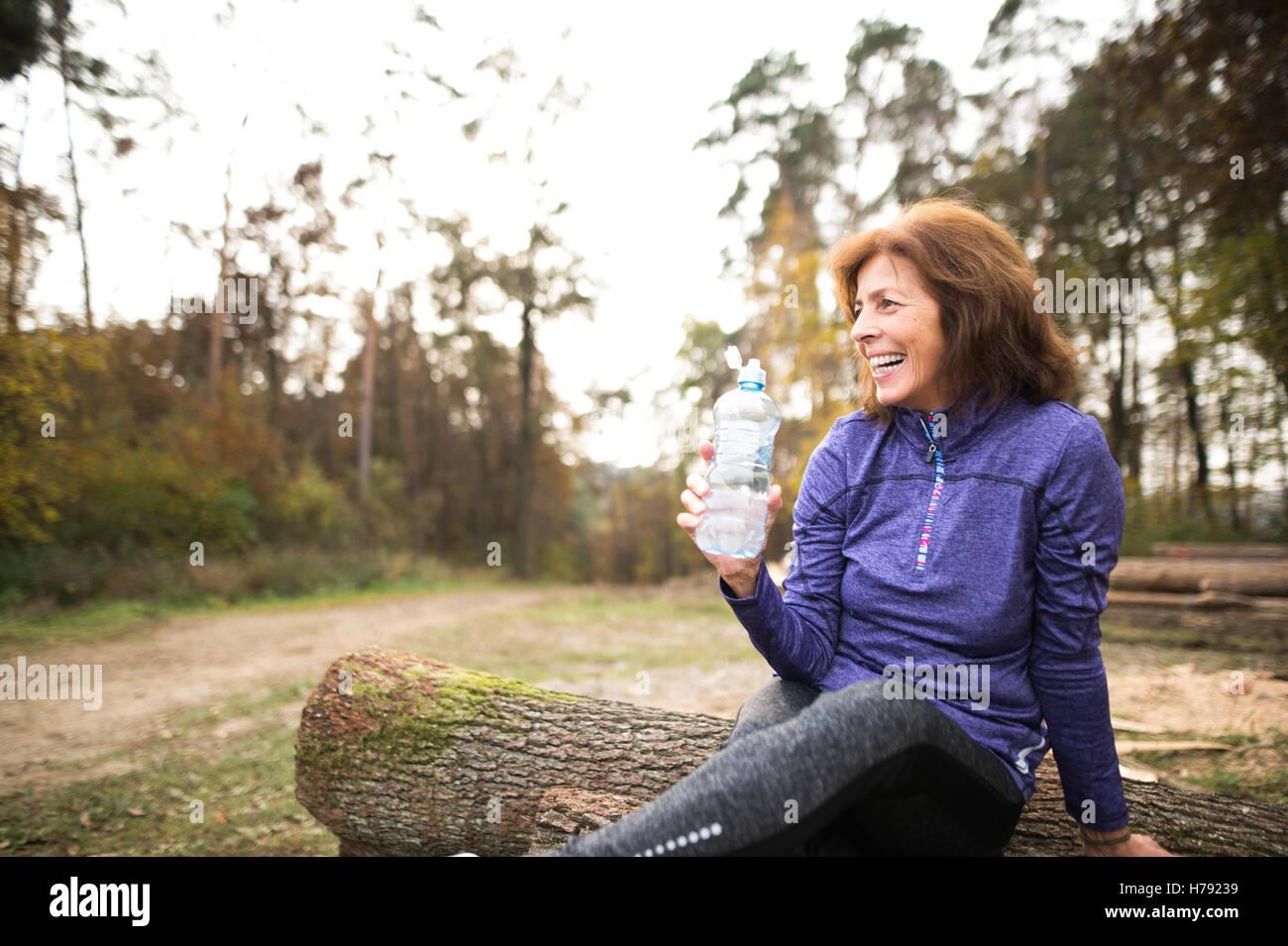Senior runner sitting on wooden logs, resting, drinking water. - Stock Image