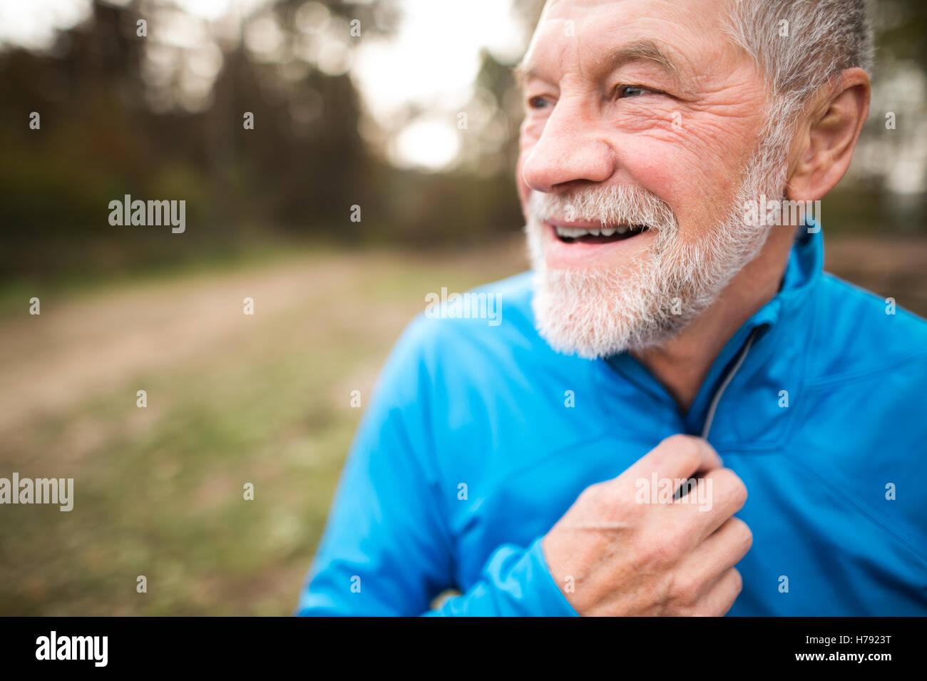 Senior runner in nature. Man resting, smiling. Close up. - Stock Image