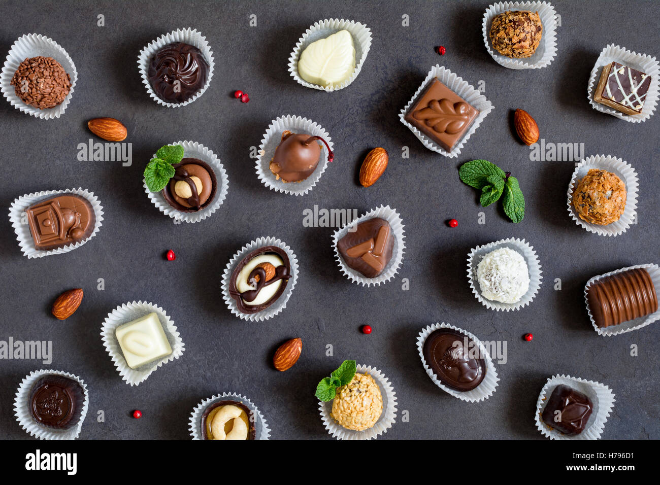 Fine chocolates pattern on dark background - Stock Image