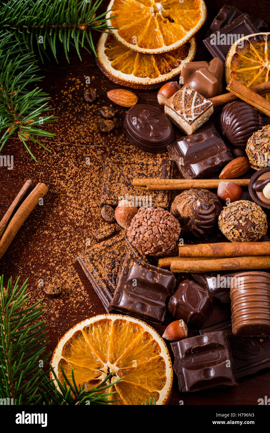 Christmas sweets: assortment of chocolates, truffles, candies, chocolate barks, spices and nuts. Christmas spirit - Stock Image