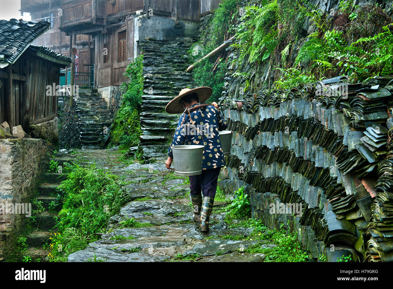 A woman walks carrying a balancer along the stone streets of her wood Tang'an village over Zhaoxing Stock Photo
