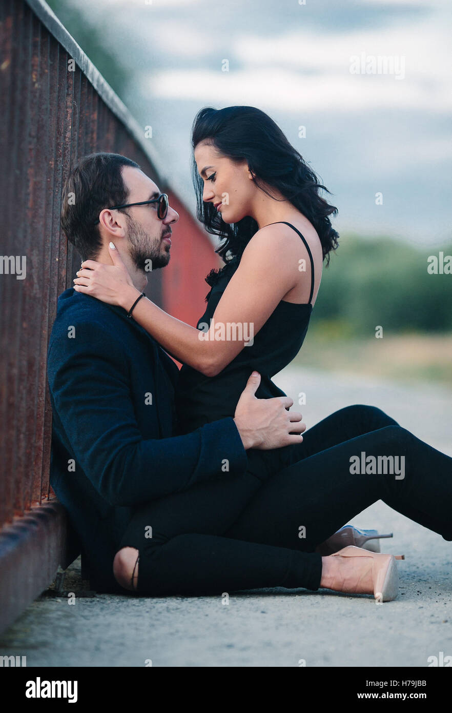 girl sits on a guy - Stock Image