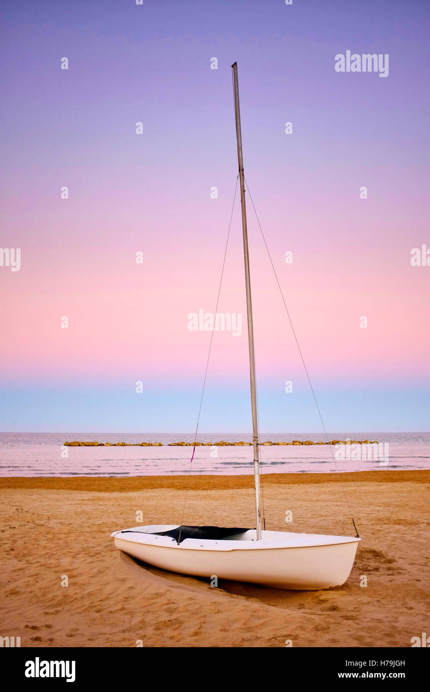 Sailboat on a shore during sunset - Stock Image