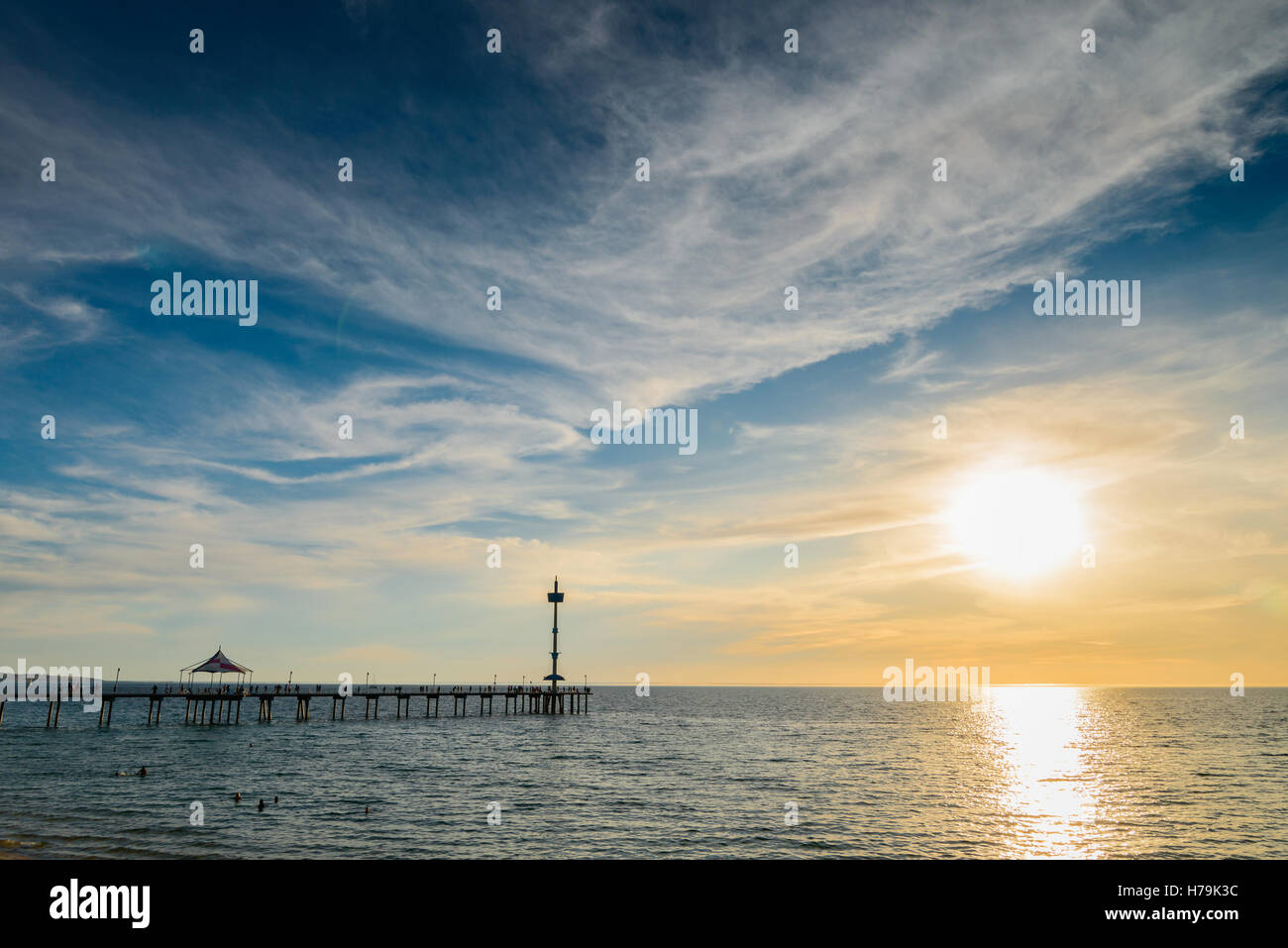 People on Brighton Jetty at sunset on a summer evening - Stock Image