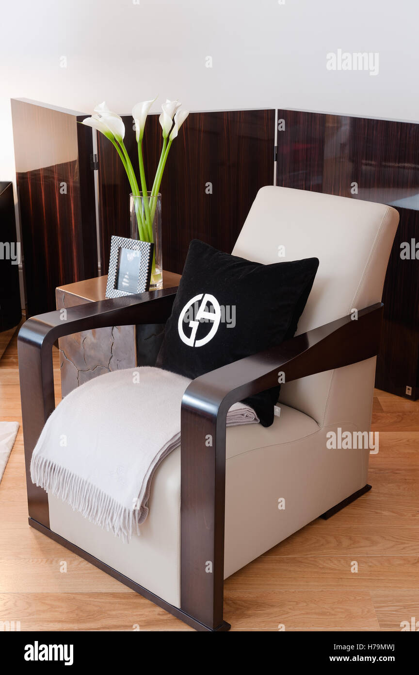Black cushion with symbol on dark wood polished armchair with half-folding-screen - Stock Image