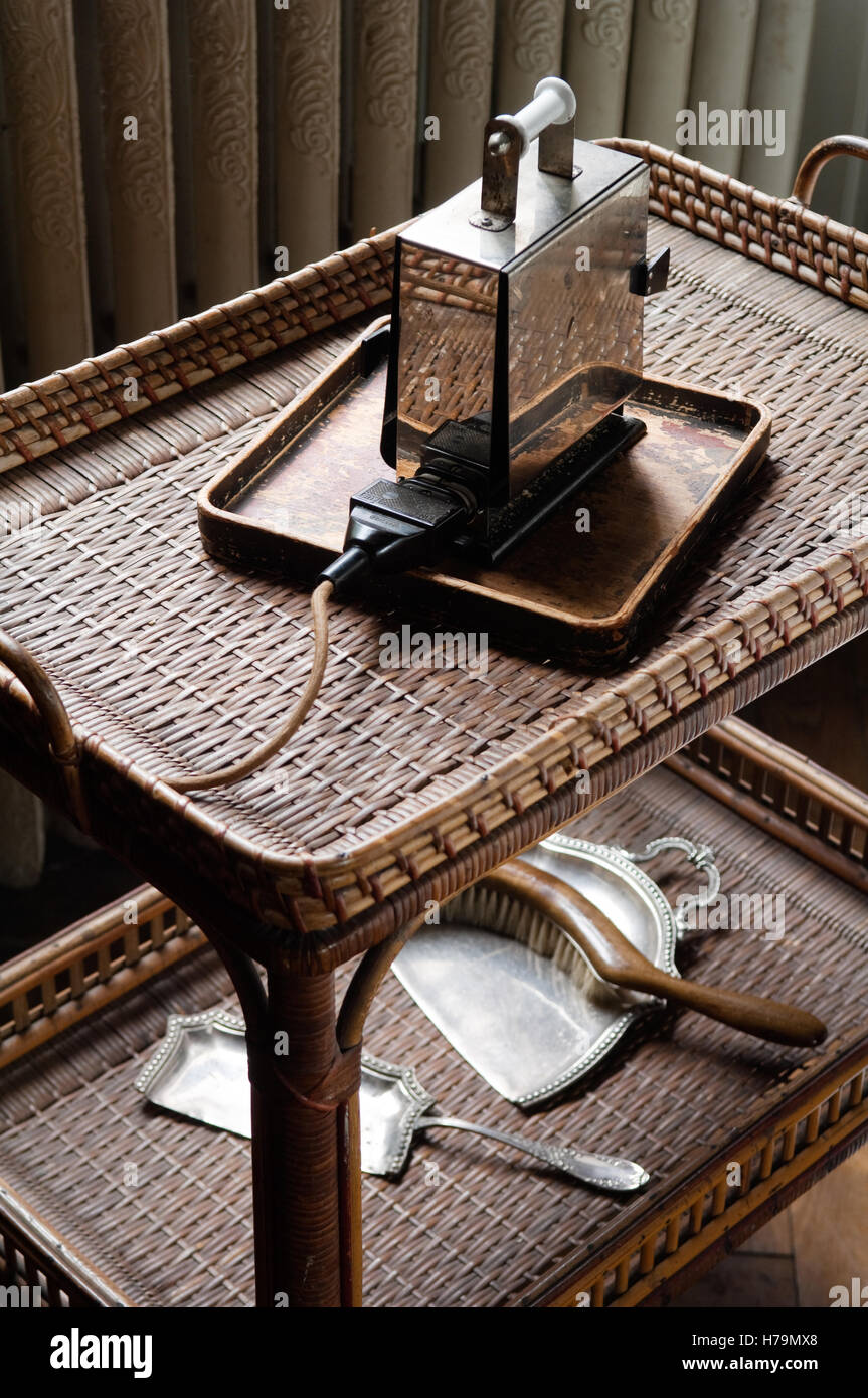 Electrical appliance and dustpan with table-brush on wicker service trolley in 18th century Chateau de Cussigny, - Stock Image