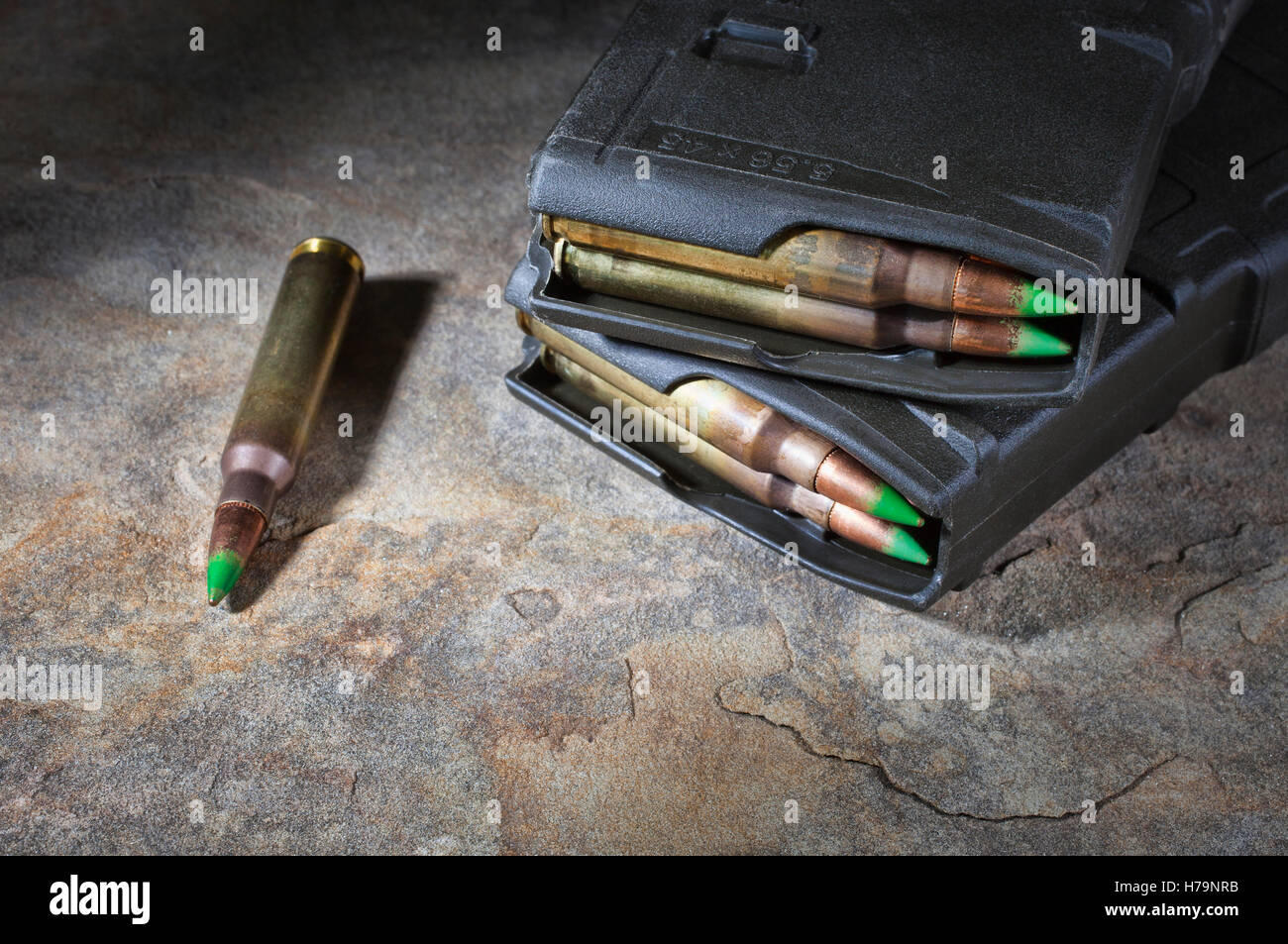 Rifle ammunition and magazines with a green tip and bullets with steel inside Stock Photo