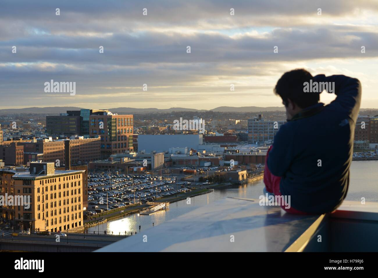 A Man Sitting On Ledge Of Skyscraper Overlooking City At Sunset