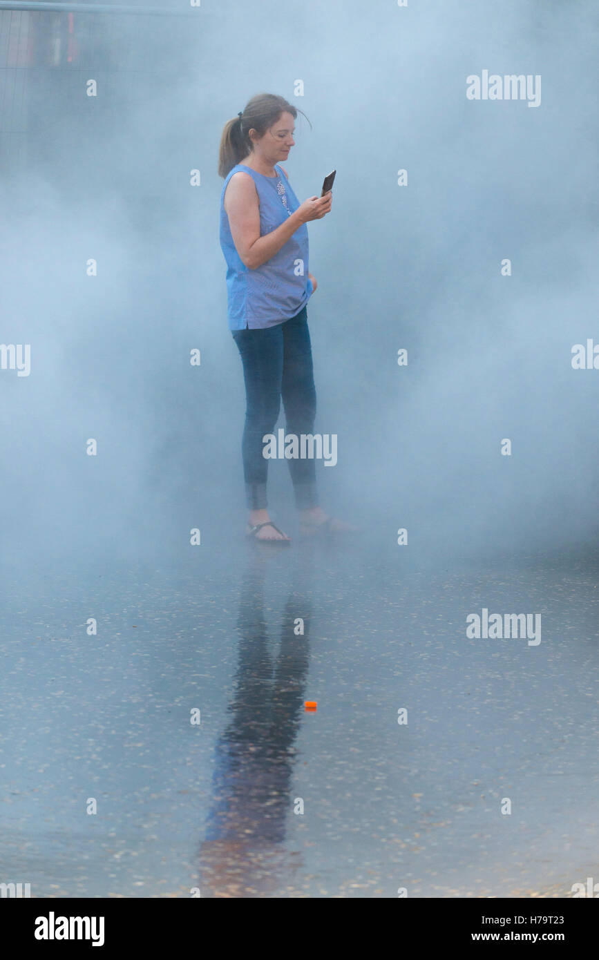 London Southbank Tate Modern water mist work of art feature girl woman lady female takes selfie in mist - Stock Image