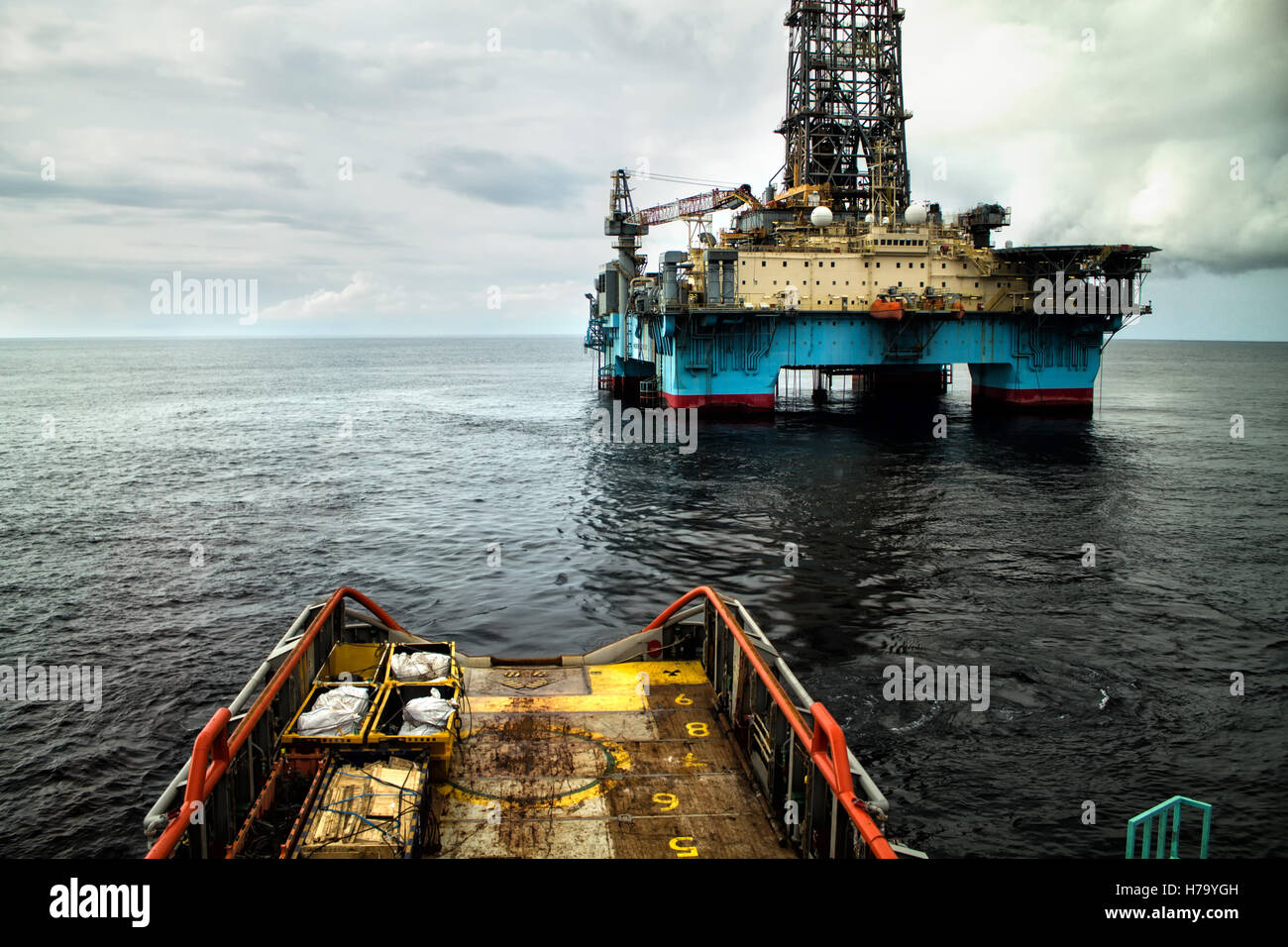 Anchor-handling Tug/Supply (AHTS) vessel during dynamic positioning (DP) operations near Oil Rig. Stock Photo