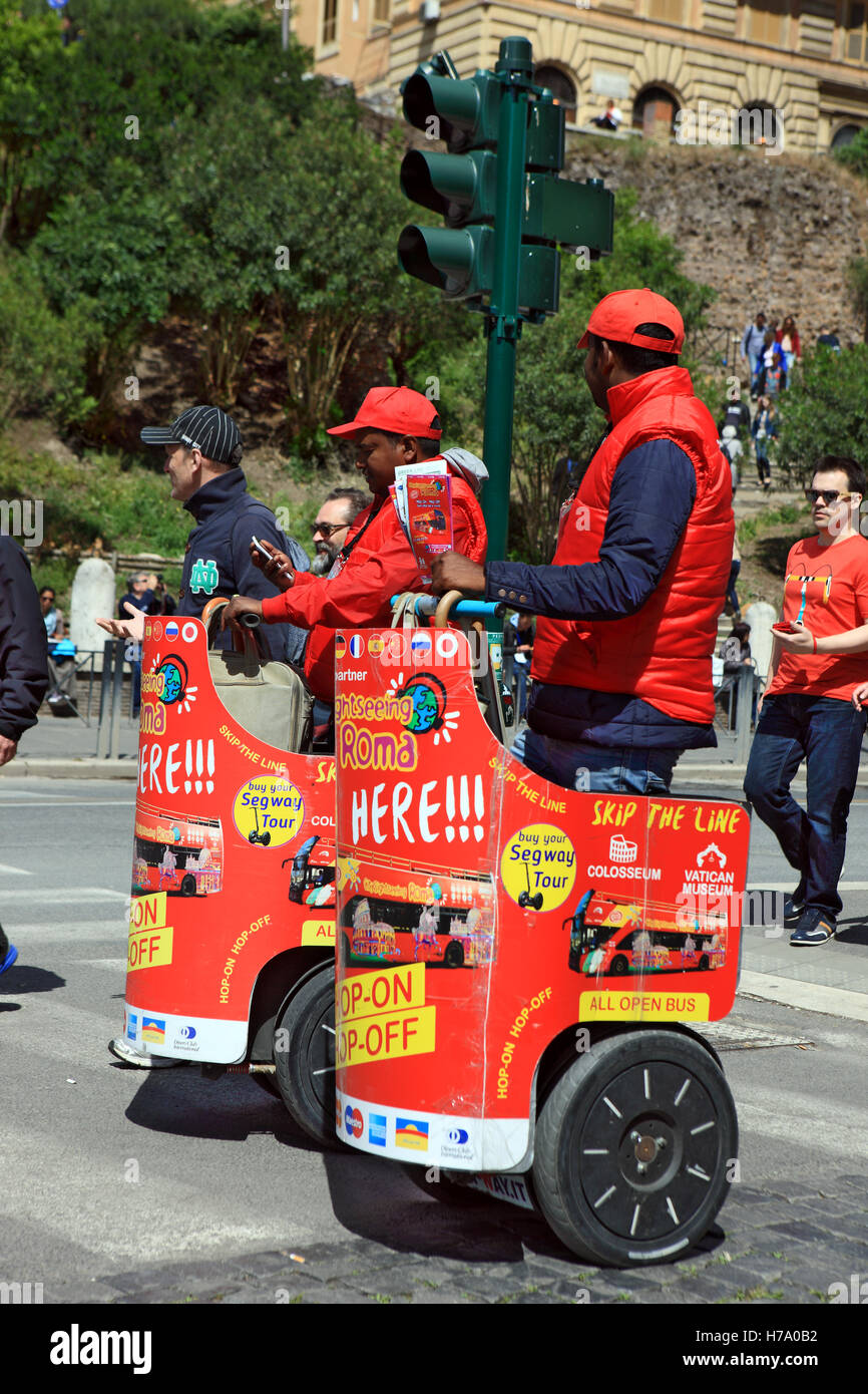 Ticket sellers on Segways outside the Colosseum in Rome, Italy selling tourists hop-on hop-off sightseeing tours - Stock Image