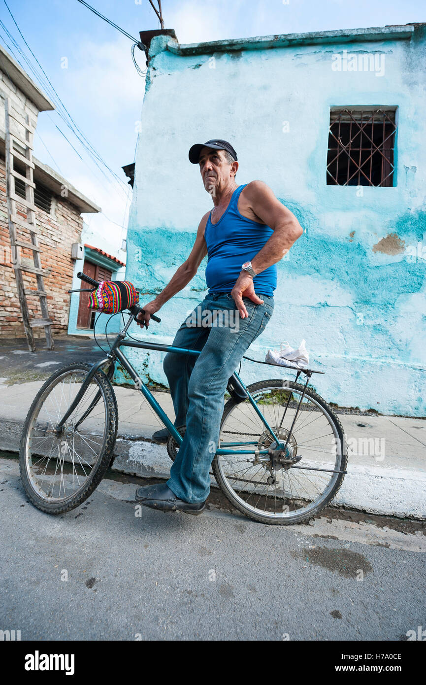 HAVANA - JUNE 12, 2011: Cuban man pauses while riding a bicycle on a street in Central Havana. - Stock Image