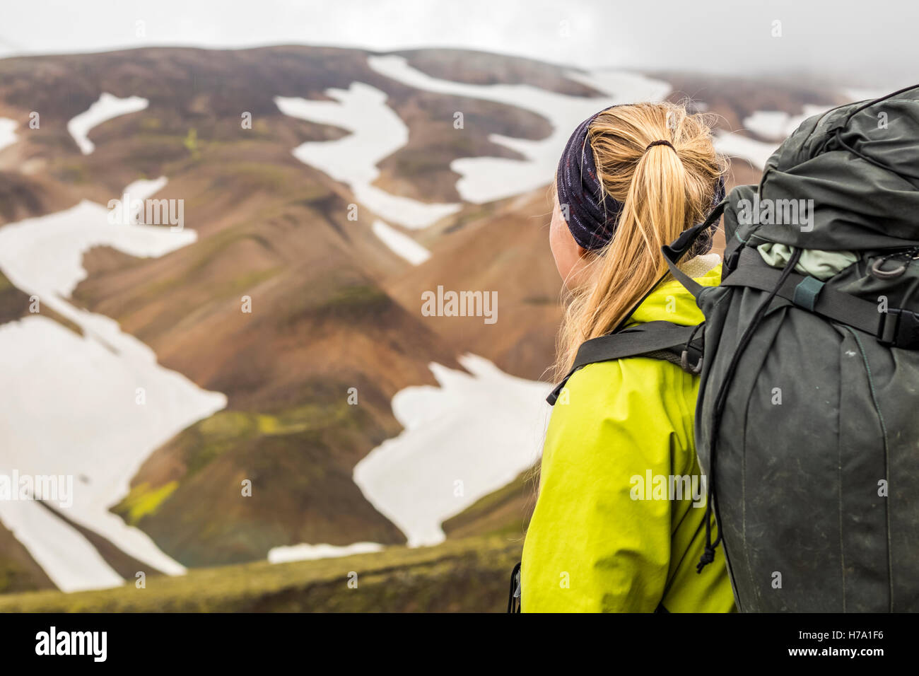 A young hiker overlooking the mountains in Landmannlaugar. - Stock Image