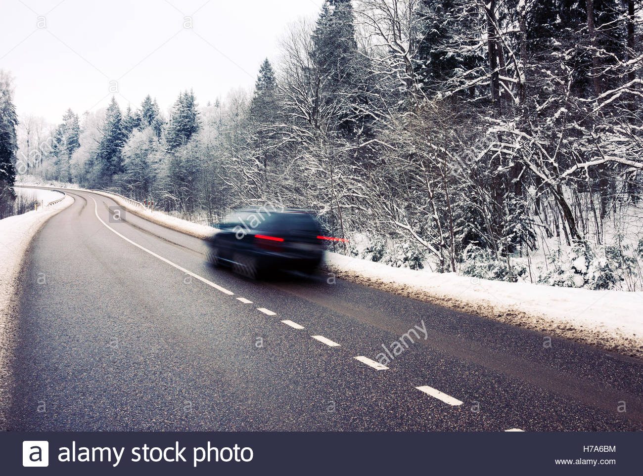 Lonely car in motion blur on the road in winter landscape - Stock Image