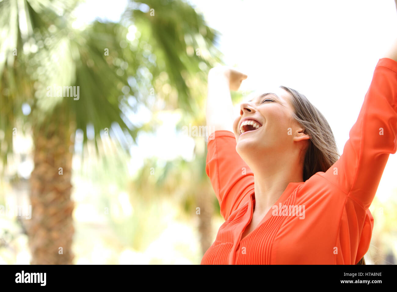 Portrait of an excited woman with eyes closed raising arms skyward outdoors with palm trees in the background - Stock Image