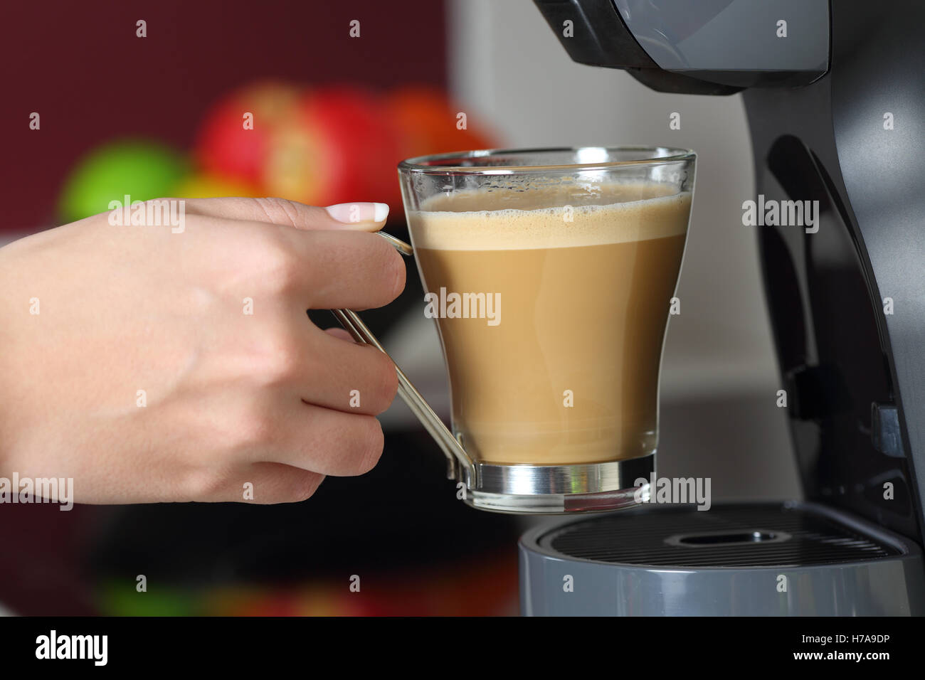 Close up of a woman hand holding a cup in a coffee maker in the kitchen at home - Stock Image