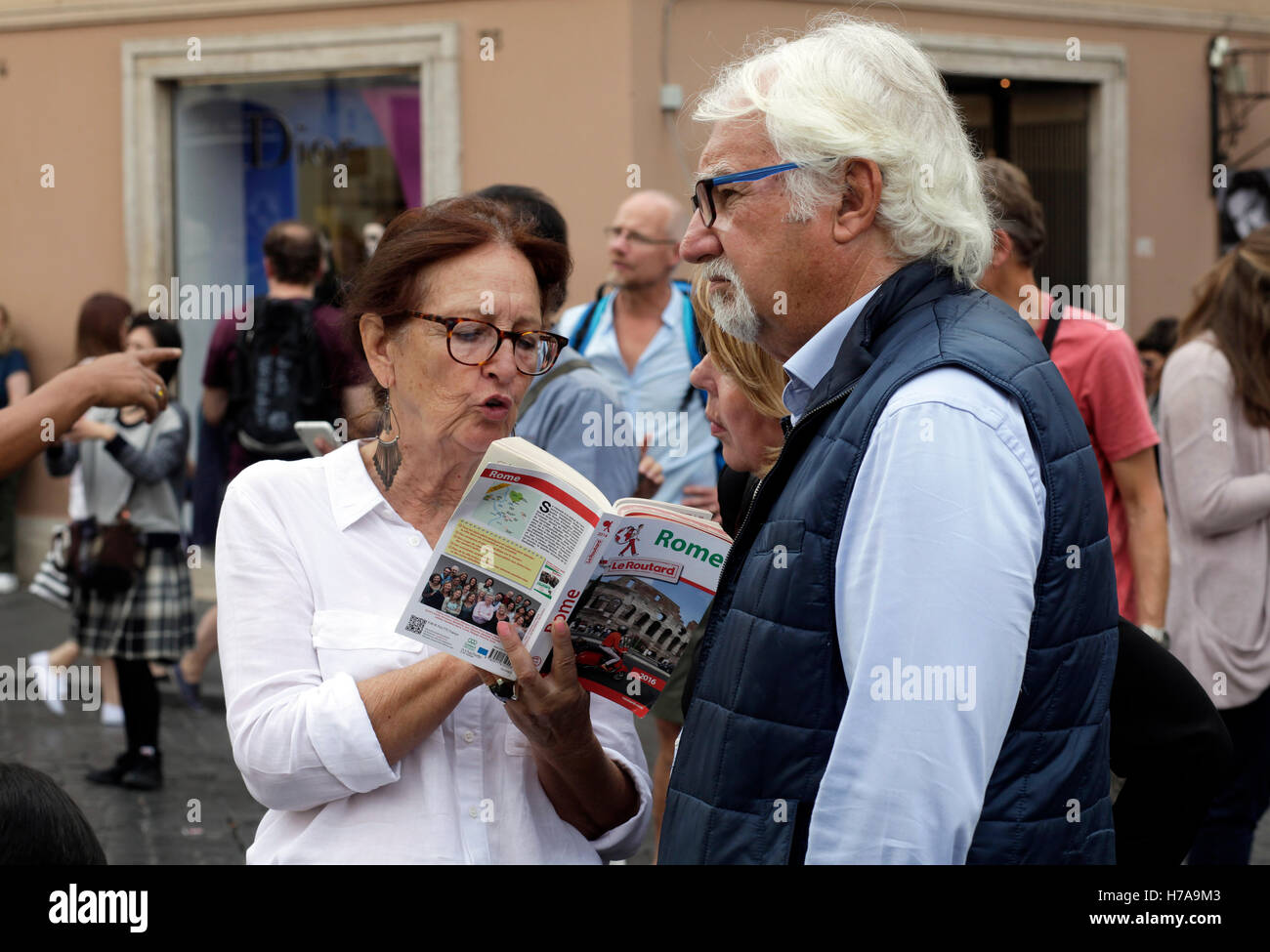 Caucasian couple reading a travel guide of Rome, Italy - Stock Image