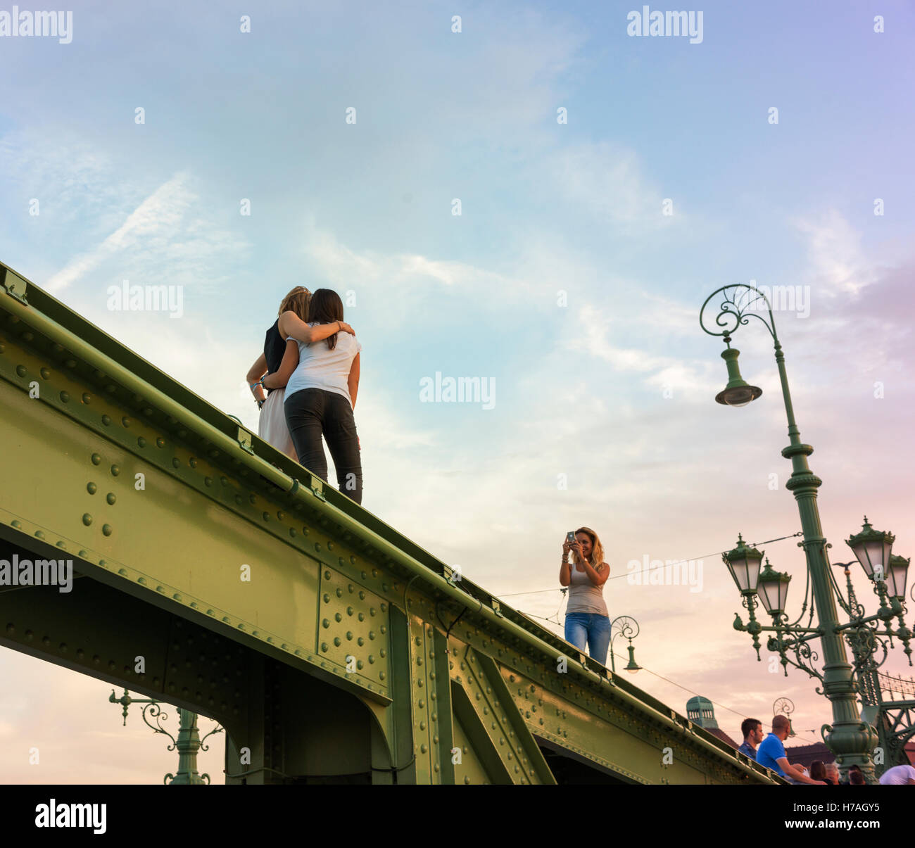 Budapest's Freedom Bridge was closed to traffic at the time so became a place where people gathered in the evening. - Stock Image