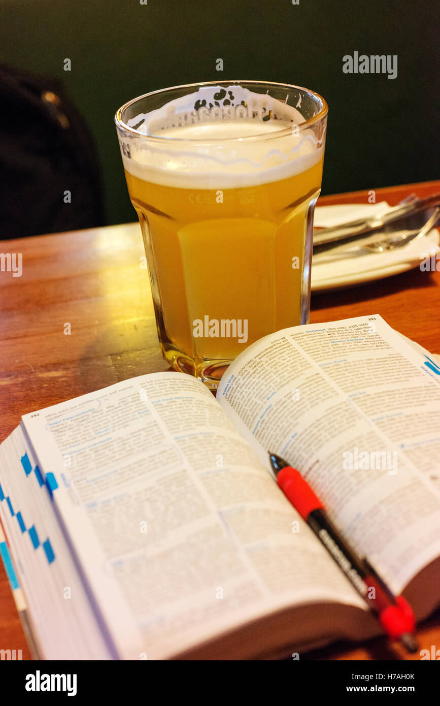 Large glass of beer drank while planning travel, with travel guide book. - Stock Image
