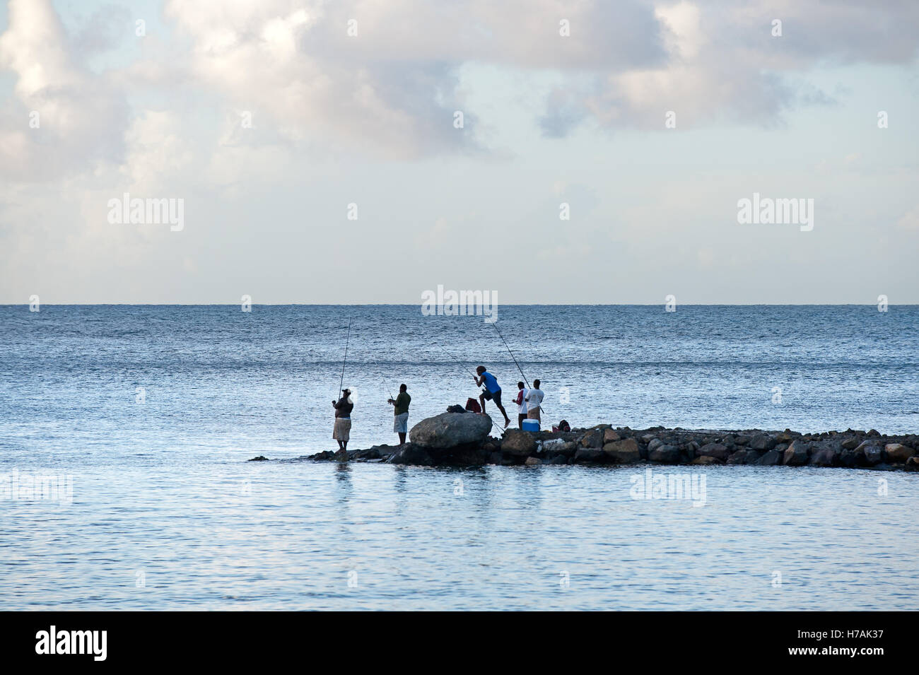 Fishermen stand with rods on promontory in St Lucia with view of horizon to sea. - Stock Image