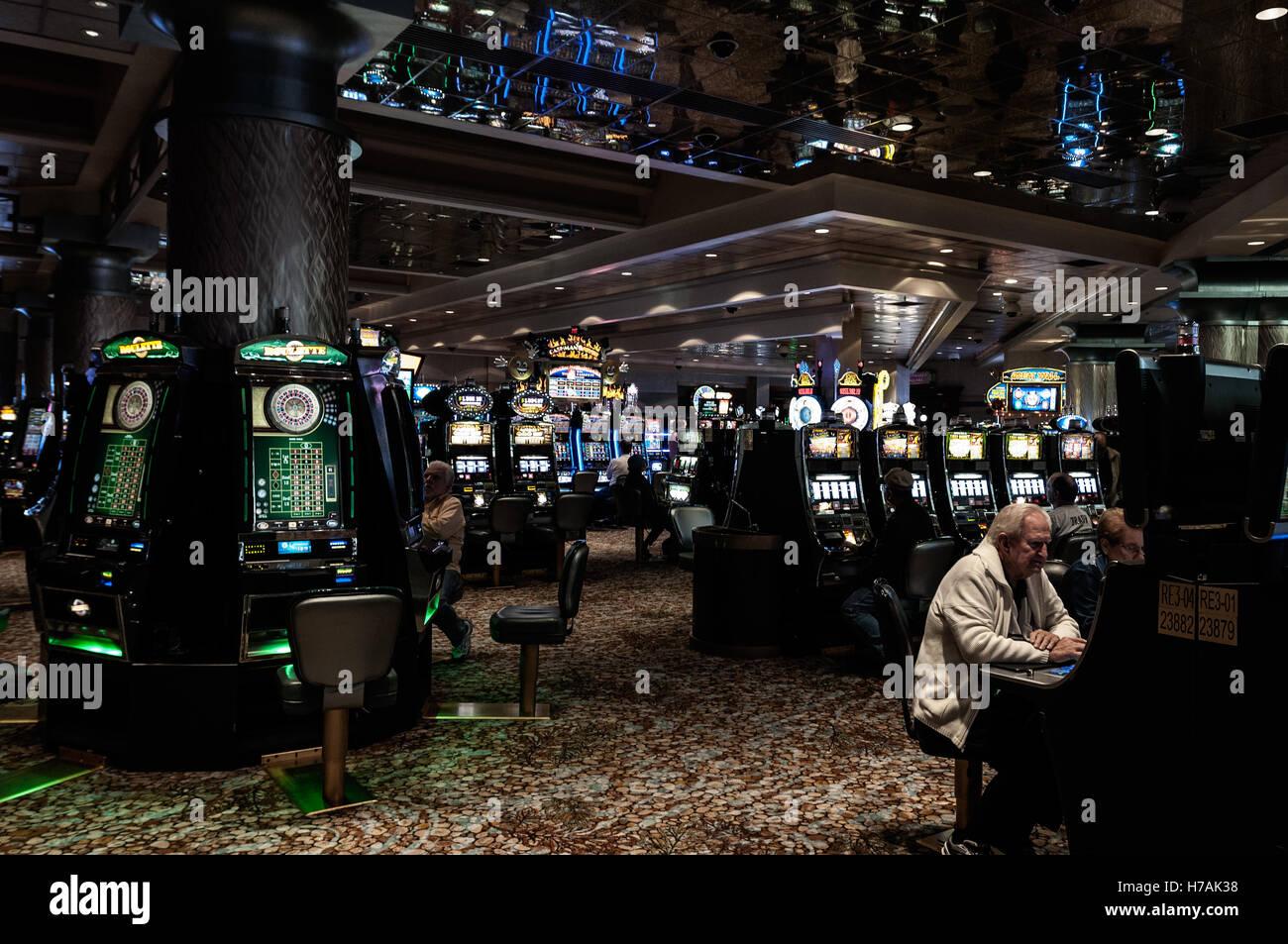 Men sit gambling at slot machines, Foxwoods Resort Casino interior, Ledyard, Connecticut, USA - Stock Image