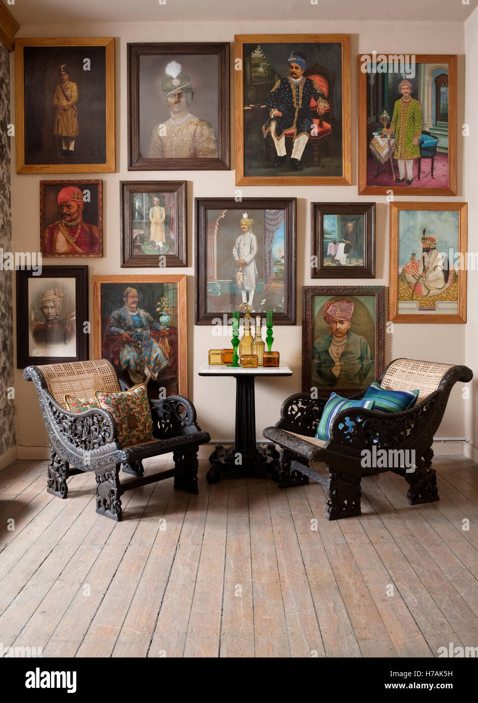 Ornately carved wood Indo-portugese caned easy chairs in room with wooden flooring and Indian maharaja portraits - Stock Image