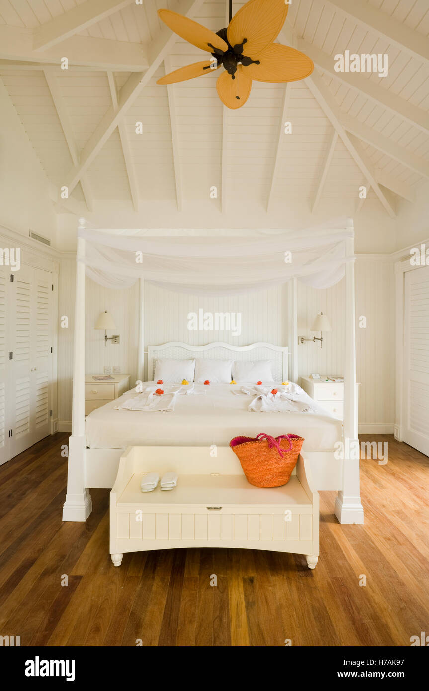 White four postered bed with yellow ceiling fan in st lucia home white four postered bed with yellow ceiling fan in st lucia home caribbean aloadofball Choice Image