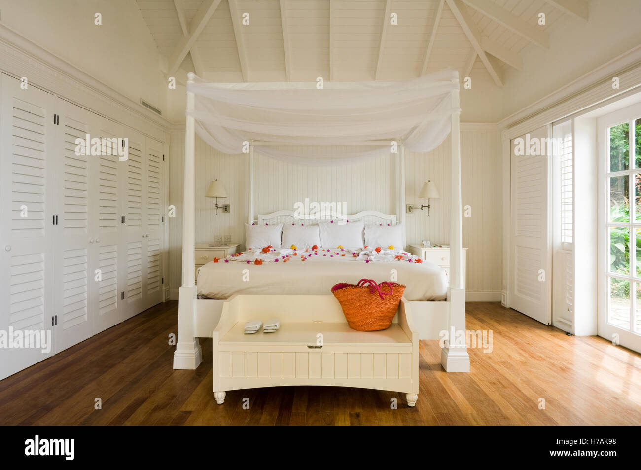 White four postered bed scattered with flower petals in St Lucia home, Caribbean - Stock Image