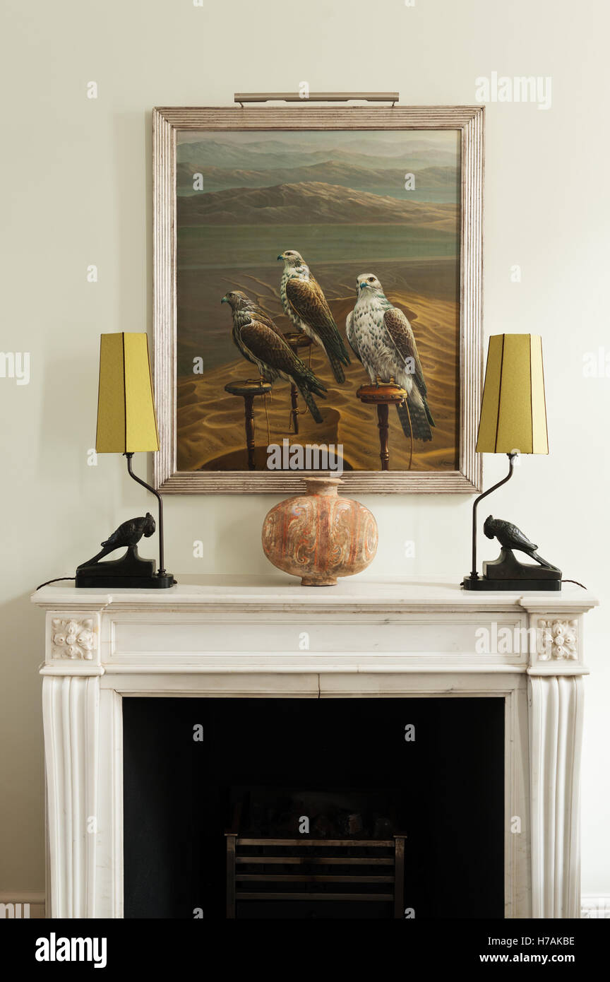 Matching lamps made from oriental artefacts on fireplace with artwork of hawks - Stock Image