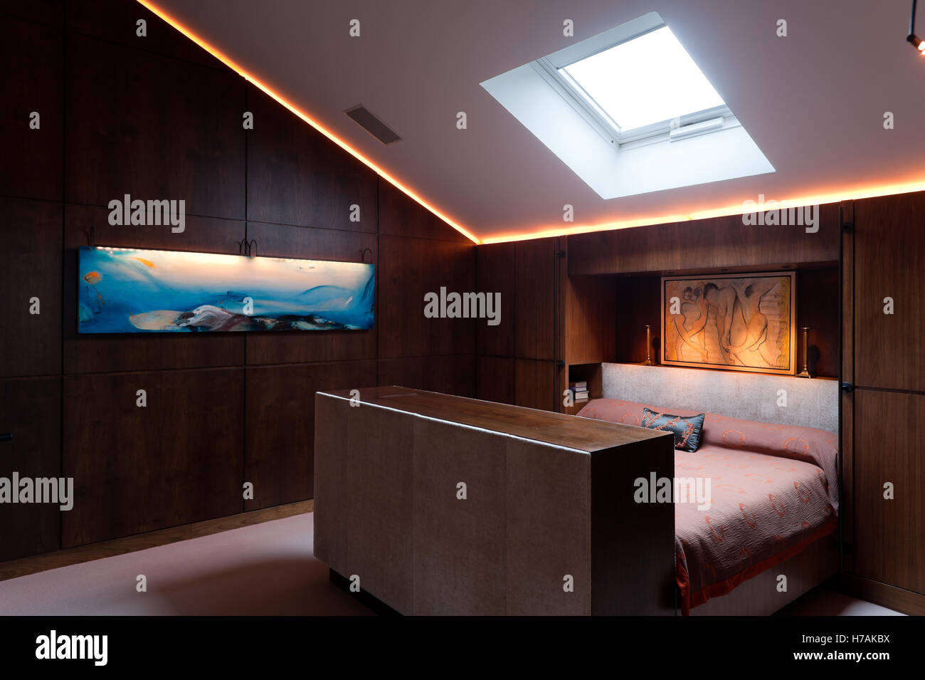 Wood panelled attic bedroom with modern arrt canvas, interior design UK - Stock Image