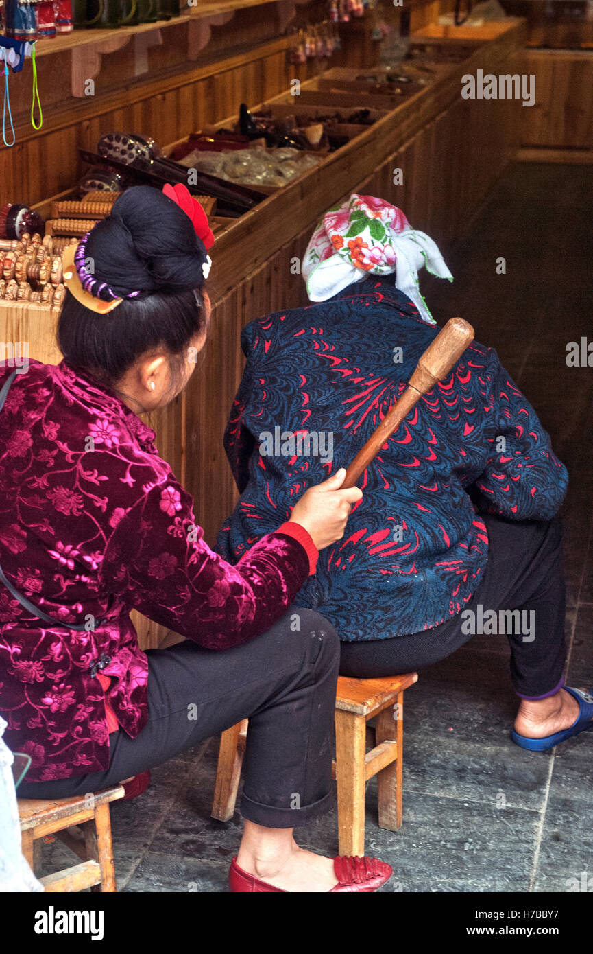 A Dong woman pats with a stick the back of her mother, in Zhaoxing village, in Guizhou province, China Stock Photo