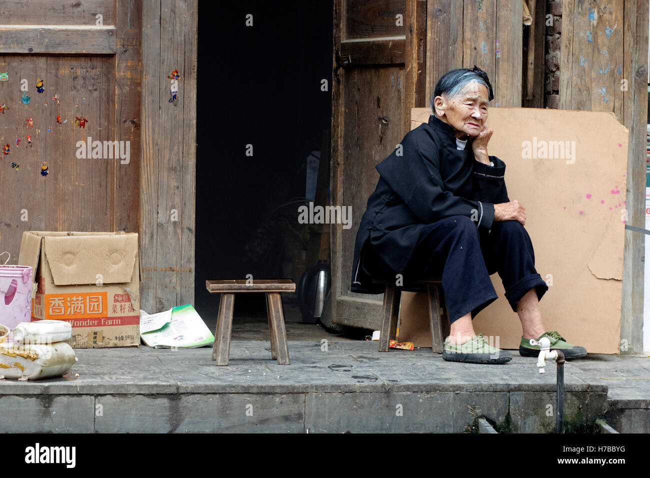 An old Dong woman sitting in front of her wooden house in Zhaoxing village, in Guizhou province, China Stock Photo