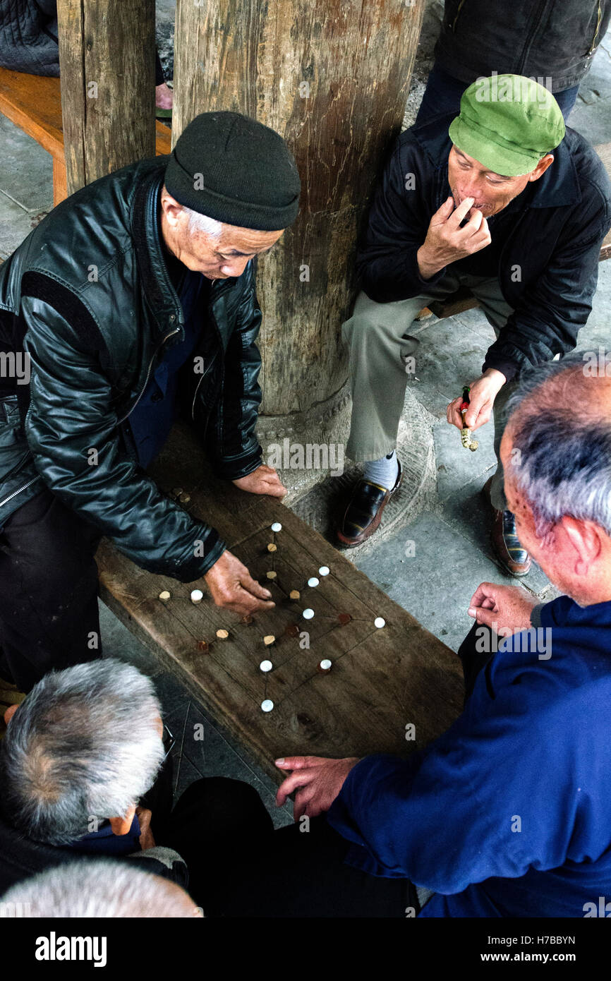 Old men play to a Chinese checkers on the streets of Zhaoxing village, in Guizhou province, China Stock Photo