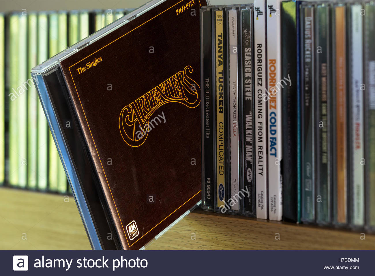 The Carpenters Singles 1969-1973 CD being chosen from a shelf of other CD's Stock Photo