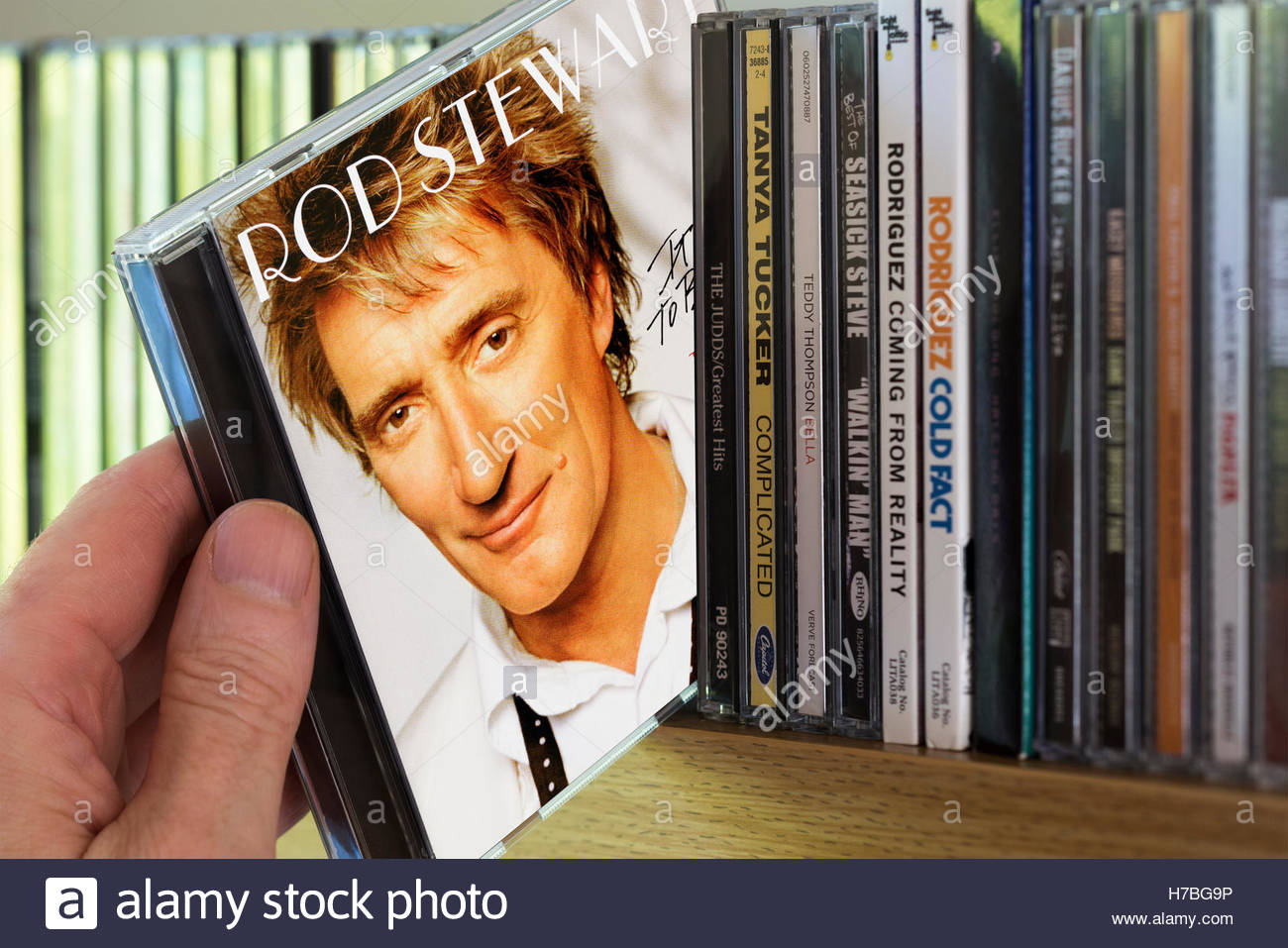 The Story So Far, The Very Best Of Rod Stewart CD being chosen from a shelf of other CD's Stock Photo