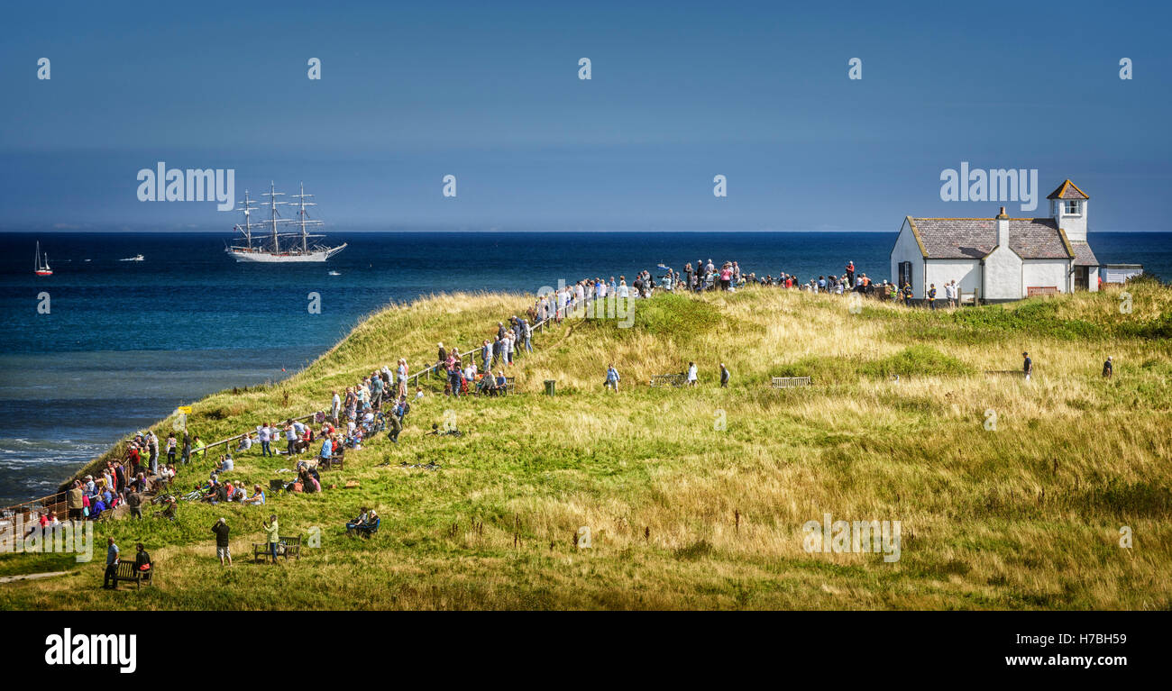 Spectators watching the tall ships race from Seaton Sluice - Stock Image
