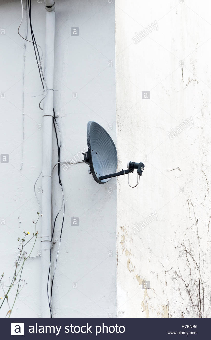 Satellite dish on the wall of a house, Blandford Forum, Dorset England UK - Stock Image