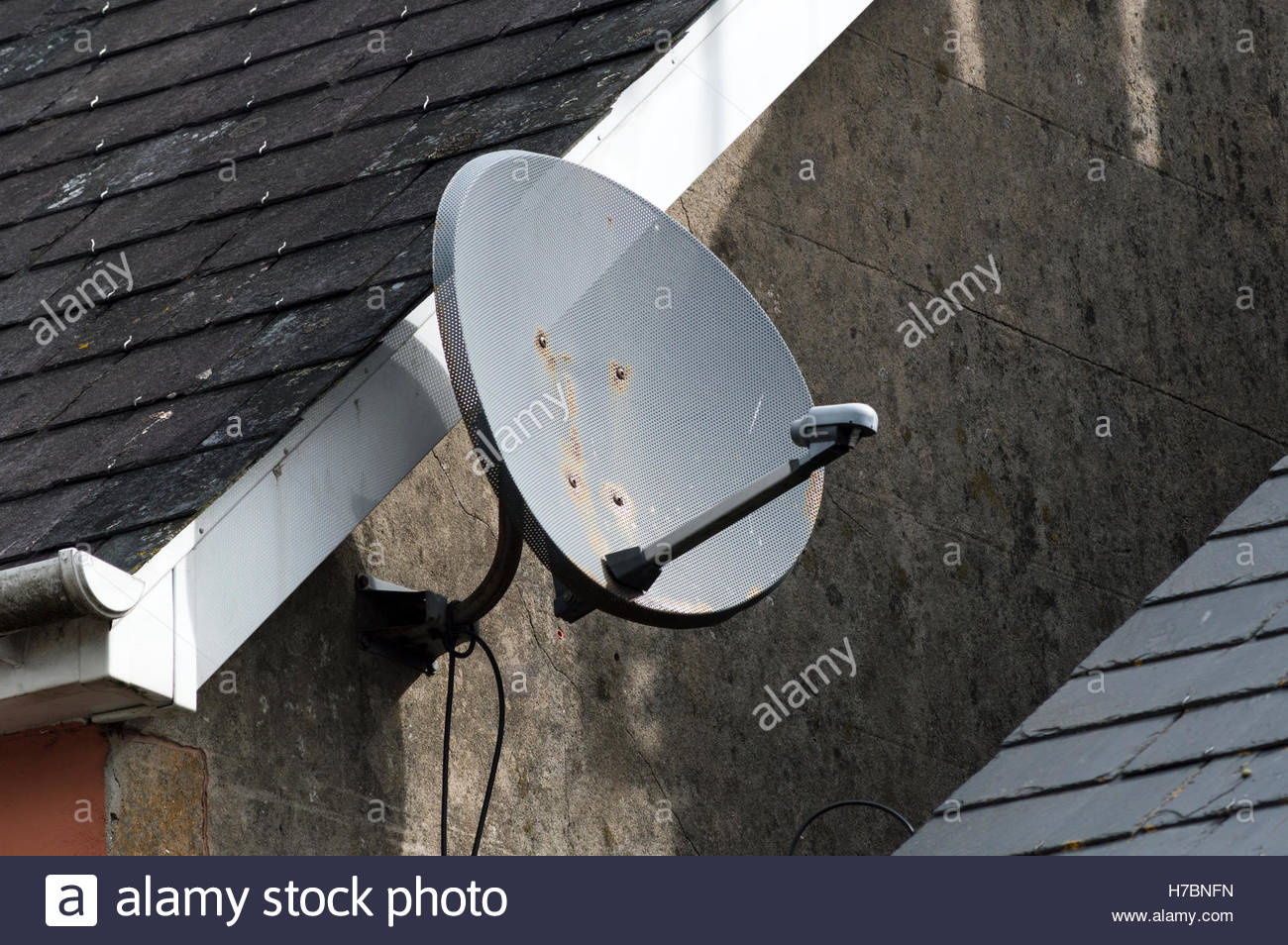 Close-up of a satellite dish on the end wall of a terraced house, Blandford Forum, Dorset England - Stock Image