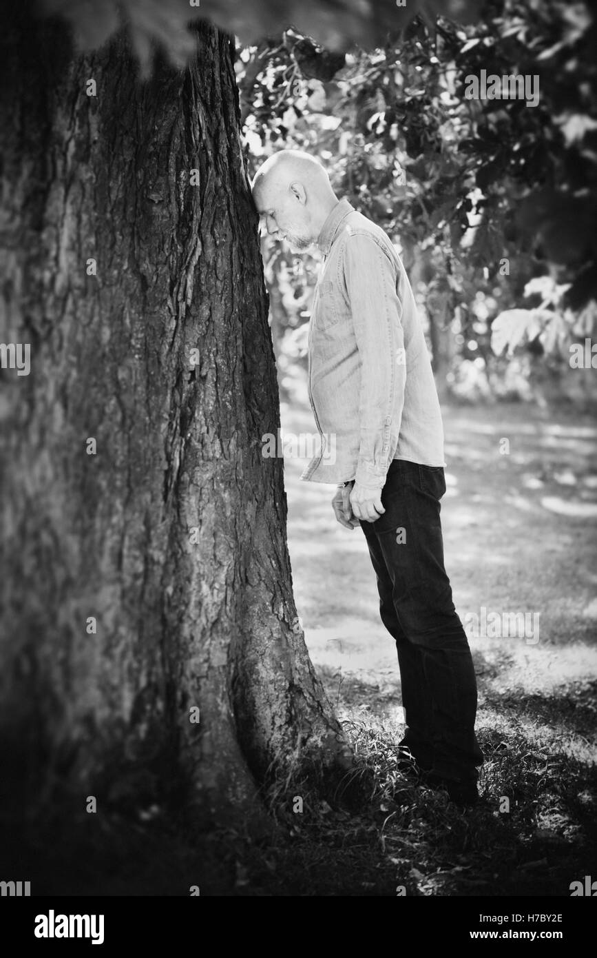Portrait of old man leaning against a tree. Concept of old age and nature. Retirement and frustration. - Stock Image