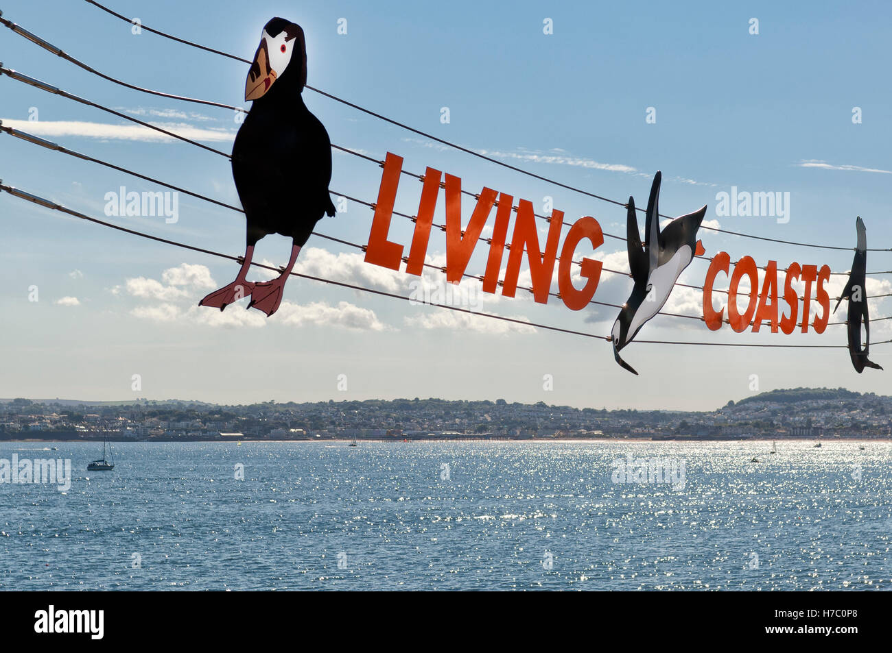 Colourful suspended sign for 'Living Coasts' in Torquay, Devon UK against a sunny blue sky in Summer. - Stock Image