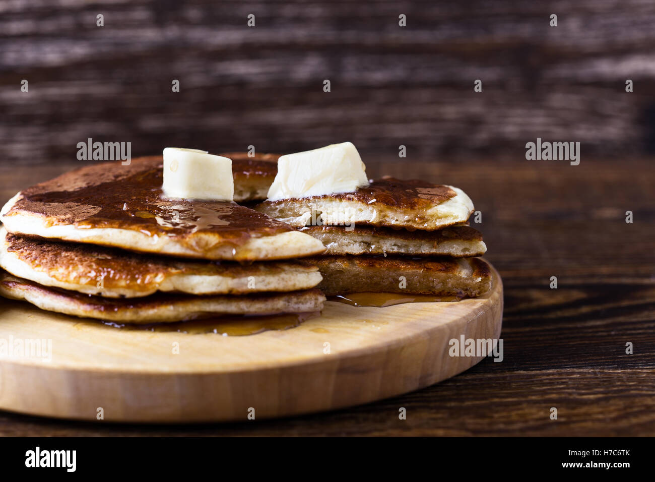 Homemade pancakes served warm with butter and maple syrup on rustic wooden table - Stock Image