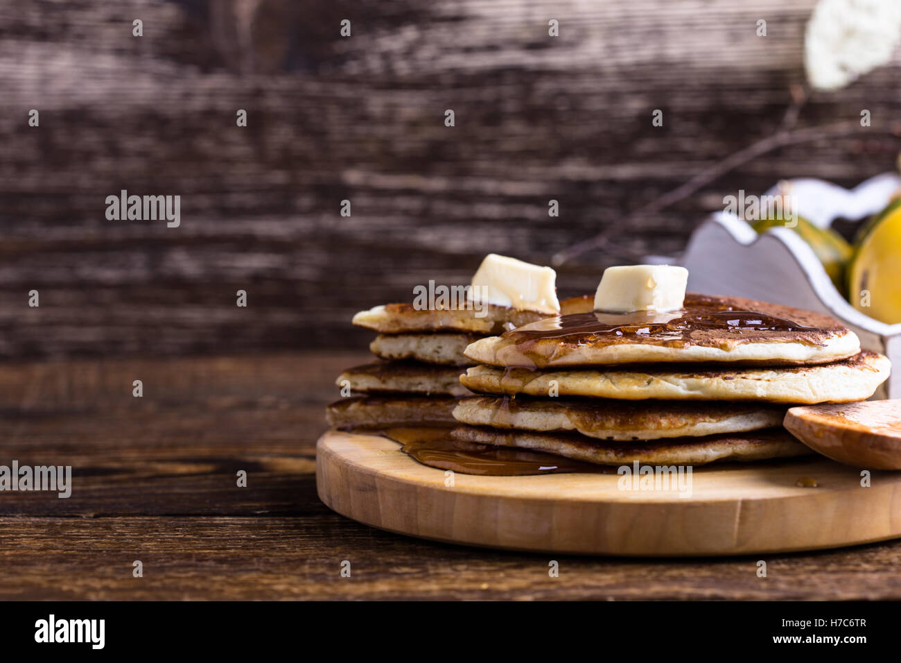 Homemade pancakes served warm with butter and maple syrup on rustic wooden table Stock Photo